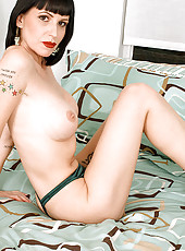 Tattooed MILF gets her rocks off on bed