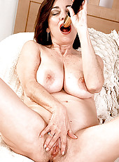Wild MILF enjoys her black dildo in bed