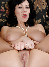 Busty nude cougar plays with her wet shaved pussy on the sofa till she gets off