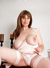 Busty milf spreads her pink pussy wide open on the table and flaunts her big tits