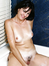 Alluring cougar Katie fucks her sweet pink pussy with a clear glass dildo in the bathtub