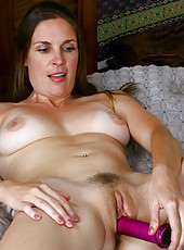 Anilos Laila fucks her cougar snatch with a purple toy in bed