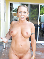 Hot mom with massive tits enjoys her pool while floating around naked with a finger in her mature pussy