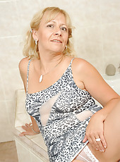 Busty granny fucks her mature pussy making herself wet in the bathroom