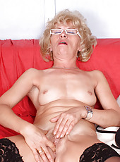 Lonely naked mature housewife Susan Lee comforts herself by fingering her Anilos pussy on the sofa