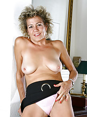 Sophisticated Anilos milf takes off her panties and lifts up her skirt to show us her hairy pussy