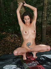 Horny mature hippy Simone spreads her long legs in the backyard