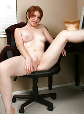 Short haired MILF with a shaved pussy spreads her legs at work