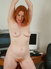 Redheaded Rose plays around with her furry pussy at the office