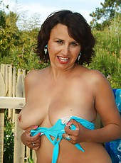 Mature MILF spreads her pussy in the garden