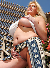 Blonde Tahnee Taylor showing off her massive melons in the backyard