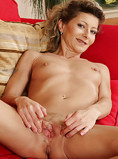 Petite and mature Syndi Bell tugs at her small pussy on the red sofa