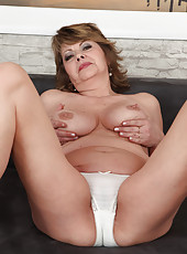 53 year old Donna Marie reclines on the couch massaging her pussy