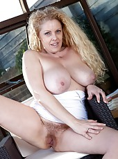 Teya is a natural hairy woman who is outside by her greenhouse when she slowly starts slipping off her clothes. First her big tits flop out then she presents her full hairy pussy.