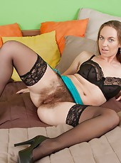 She looks really sexy in her black lingerie, especially her black nylons. But when she takes everything off and breaks out her purple toy, she is super hot with it in her hairy pussy!