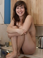 Slender brunette Nixi strips seductively in the kitchen before mounting the bench top and showing of her wonderful hairy pussy and natural body.