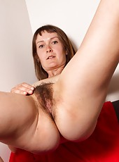 As soon as Charlotte B gets home from work she site on the couch and gets out her bush and big red dildo. She simply cant wait to push it deep inside her furry pussy