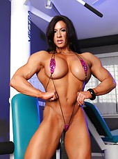 Angela Salvagno is wearing a tiny sling bikini that shows off all of her bulging muscles, the bikini is so small it barely covers her meaty pussy lips and large clitoris.