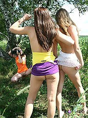 Three chicks posing naked outdoors in a field