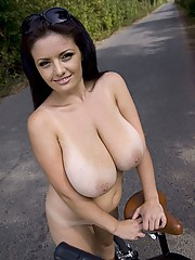 Busty brunette looks sexy on a bike ride
