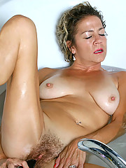 Experienced cougar Vanessa enjoys her bubble bath with a black vibrator banging her wet hairy pussy