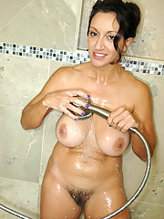 Totally naked busty milf stuffs her hairy Anilos pussy with a rabbit toy inside the shower