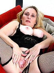 Curvy mature lady in sexy fishnet lingerie keeps her hands busy playing with her thick pussy lips