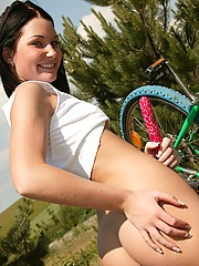 Hot teenage cutie on a bike plays with a toy