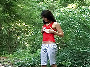 Teen in the forest enjoys playing with toy