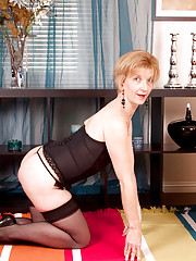 Seductive cougar milf in black lingerie bends over on the floor and flaunts her ass