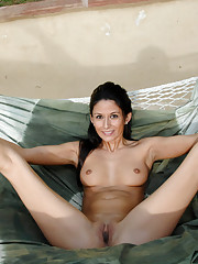 Flirty milf licks her finger and spreads her pussy in a hammock