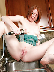 Horny cougar housewife uses the water from kitchen sink to stimulate her clit