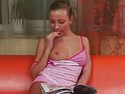 Horny beauty on the orange couch masturbating