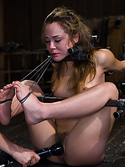 Kristina Rose is bound into metal pipe with her knees to chest and arms in strappado. Maestro fucks her face and JP torments her with rubber bands.