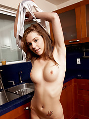 Desirable Nubile temptress wets her white tee shirt using the sink spray