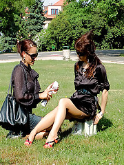 Two sexy girls outdoors fondling with cream