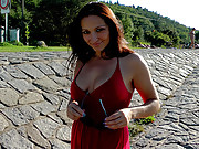 A fetish chick wearing a red dress outdoors
