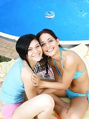Bikini lesbians caressing cooters near a pool