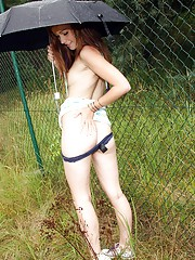 Teen beauty masturbating outdoors in the rain