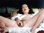 Veronica Hart masturbating in bed with a toy