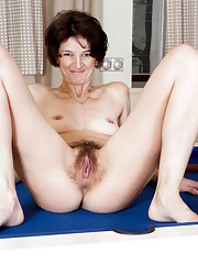Milady plays with her hairy pussy on the table