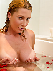 Romantic look at a housewife soaking in a tub full of rose petals