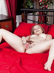 Kylie Harris strips naked on red bed