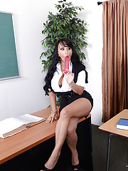 Holly Halston pulls out her big double sided dildo to show her student.  Then she helps her student get wet before they have a hot threesome in her classroom.