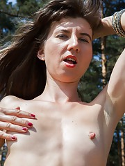 Kirina strips outdoors and masturbates by trees