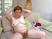 Romana Sweet strips and plays on the couch